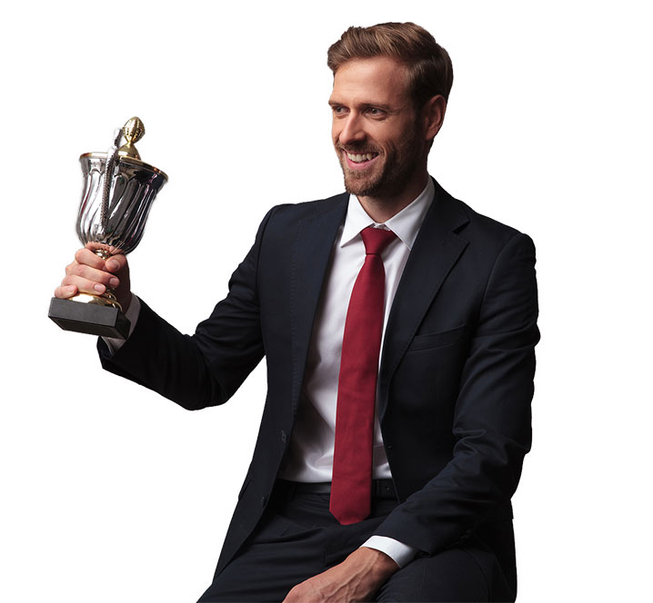 well dressed man in a suit holding up a cup trophy for corporate award