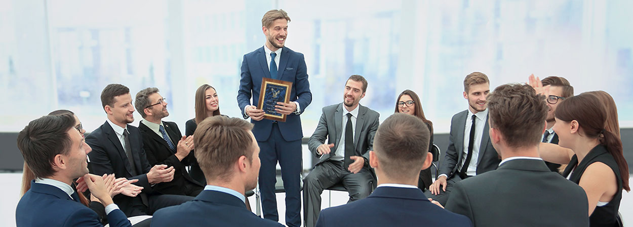 Business man accepting a corporate award plaque from other business people