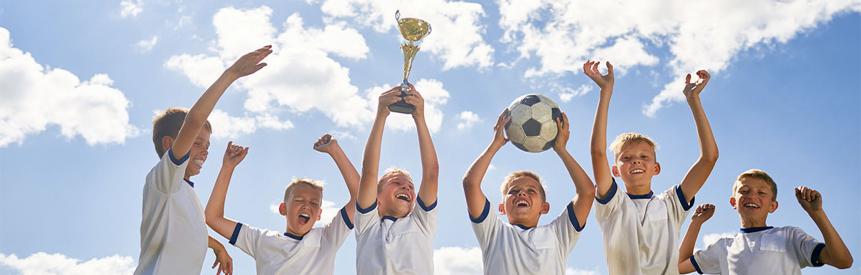 kids on soccer team celebrating holding trophy